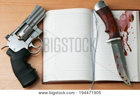 Revolver hunting knife and a open notebook on the table