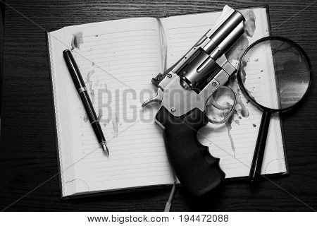Revolver open notebook and a magnifying glass on the table