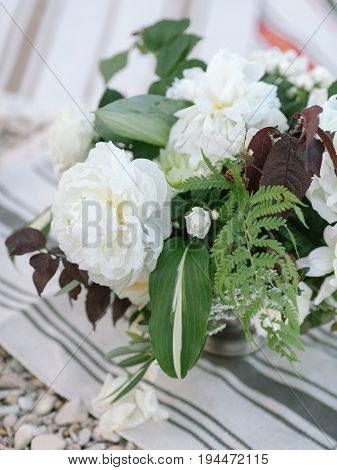 Flower composition on a on a striped rug, outdoor. beautiful bouquet of a white fresh flowers. fine art. ease, lightness concept.