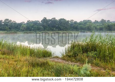 protected lakes to which the footpath conducts. Coast are covered with reed and opposite trees and bushes. Over water easy morning fog. Krasnodar Krai summer.