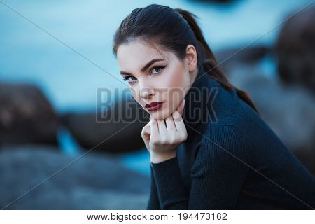 Beautiful young woman. Dramatic outdoor portrait of sensual brunette female with long hair. Sad and serious girl