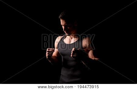 Fighter silhouette. Handsome athletic man in boxing stand on a dark background