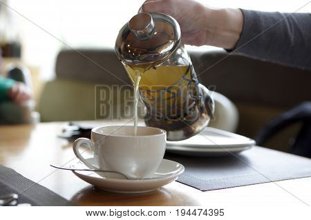 Woman pouring tea into cup in cafe