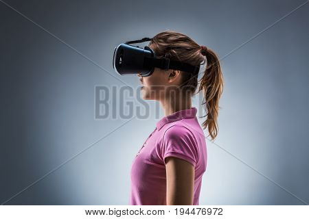 Young woman wearing virtual reality headset on a gray background. Studio shoot. Emotions. Side view