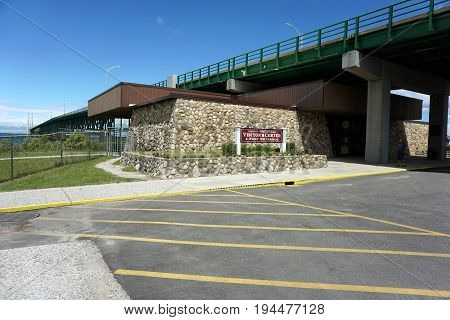 MACKINAW CITY, MICHIGAN / UNITED STATES - JUNE 18, 2017: The Colonial Michilimackinac Visitor's Center and Fort Entrance are below the Mackinac Bridge.