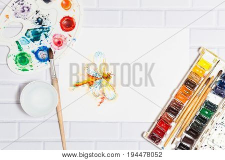 Hand Drawn Sketch of Watercolor Orange Dragonfly, with lying paints, paintbrushes and palette on the white brick background - concept of human creativity, top flat view.Have an empty place for your text