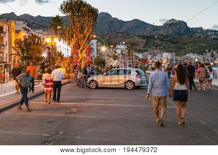Tourists Walk In Giardini Naxos In Evening