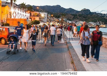 People Walk In Giardini Naxos In Evening