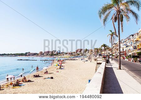 Ourists On Beach And Waterfront In Giardini Naxos