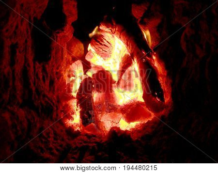 Photo of fire brown wood dark grey black coals on bright yellow fire inside metal brazier.