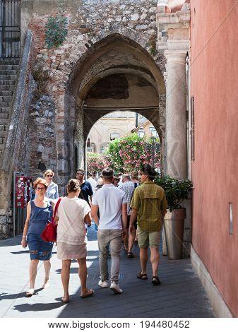 People Walk Through Gateway In Wall In Taormina
