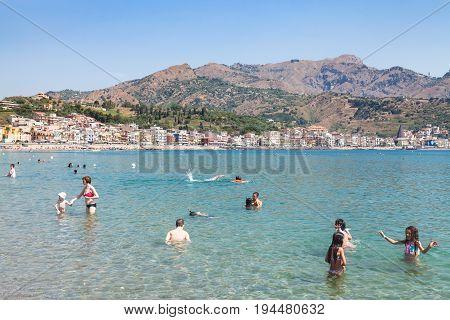 People In Ionian Sea On Beach In Giardini Naxos