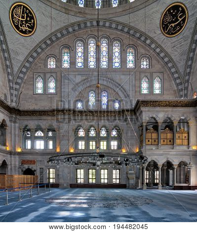 Istanbul, Turkey - April 20, 2017: Interior facade of Nuruosmaniye Mosque, an Ottoman Baroque style mosque completed in 1755, with a huge arch & many colored stained glass windows located in Fatih district