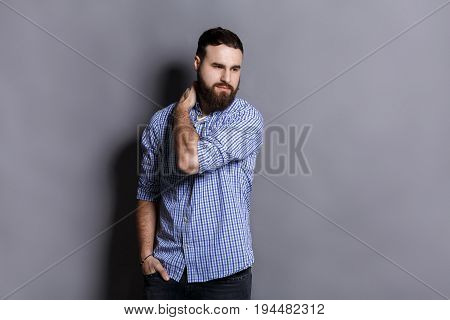 Unhappy man suffering from neck or shoulder pain. Young bearded guy holding his neck with sad expression, gray studio background, copy space