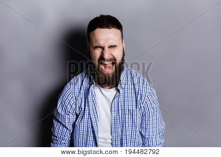 Portrait of angry crying bearded man. Aggressive guy with closed eyes screaming loudly, gray studio background. Psychotherapy exercise
