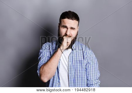 Portrait of yawning bearded man. Sleepy guy gape and close his mouth with hand, gray studio background
