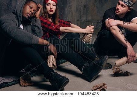 Group of homeless young people gets drunk. Youth addiction problem. Tired drunk caucasian girl holding alcohol bottle, sad and depressed guys with tattoo sits near . Social problem concept