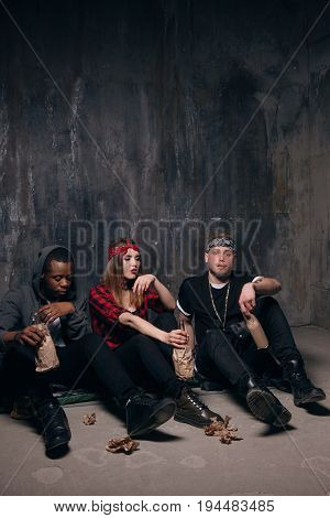 Group of unemployed young people gets drunk. Youth addiction, social problem concept . Tired drunk caucasian girl holding alcohol bottle, sad and depressed guys with tattoo sits near on the floor .