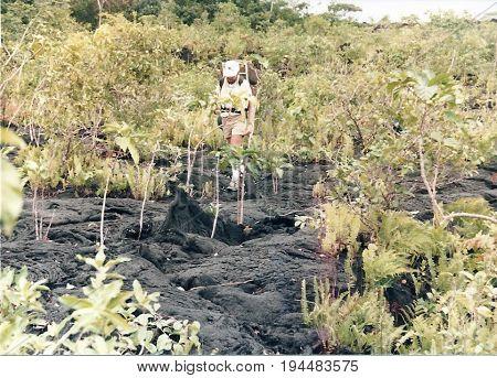 SAVAI'I / SAMOA - CIRCA 1990: An American tourist with a backpack explores a lava field.