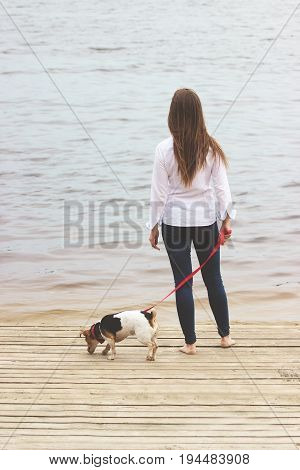 What Is Here. Full-length Rear View Shot Of Pretty Young Woman In Casual Wear Keeping Dog On Leash A