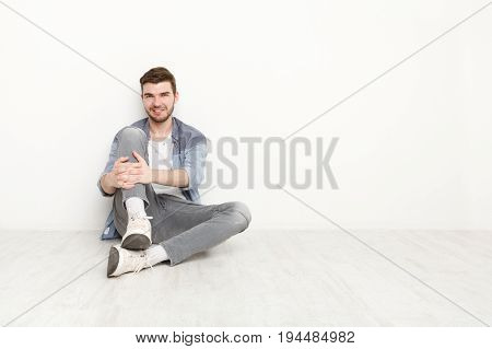 Relaxed young man sitting on floor and looking upwards. Handsome guy having rest, smiling at camera, isolated on white background