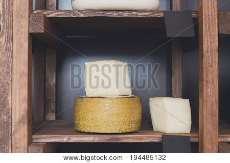 Hard goat cheese in wheel and piece on grocery shop wooden shelf, closeup