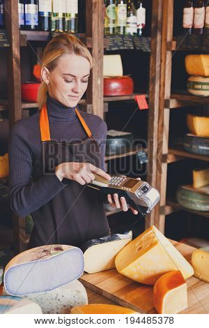 Retail, credit card payment service. Female shop assistant conducts a payment with credit card for order of cheese in grocery shop.