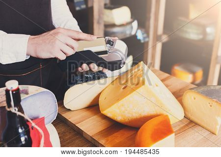 Cheese shop assistant swipe credit card at counter, paying for order in grocery