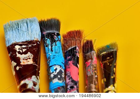Vintage Artists Brushes With Paint On An Yellow Background.closeup.copy Space