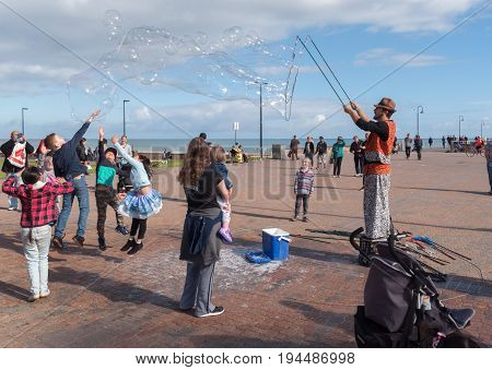 Adelaide, SA, Australia - June 12, 2017: Busker at seaside entertains crowds by blowing soap bubbles of various sizes.