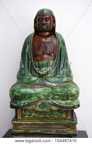 LONDON, ENGLAND - May 24,2017: sculpture (stoneware with green and brown glazes) seated Bodhidharma, ming dynasty, was buddhist monk, first chinese patriarch, Victoria and Albert Museum, London, UK