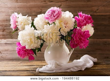 bouquet of colorful peonies flowers in a white jar on wooden table