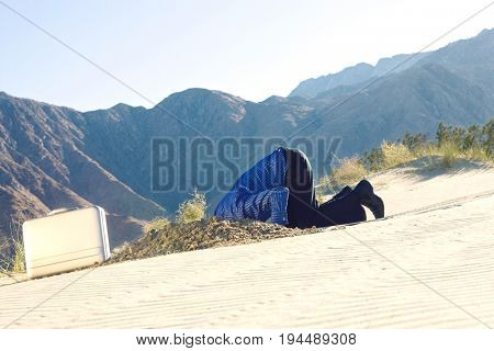 Side view of a middle aged businessman digging through the sand in desert