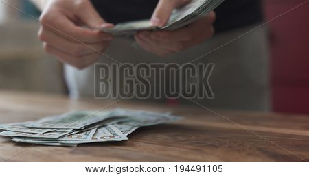 front shot of man counting dollars on wood table, wide photo