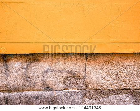 Part of building exterior with yellow background wallpaper and cement blocks.