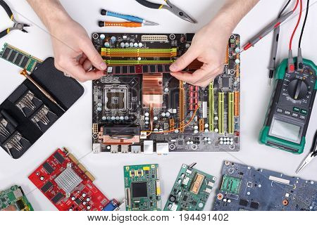 Technician upgrade of computer top view. Renovation microchip component in motherboard. Maintenance support and repairing service concept.