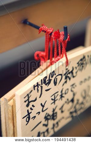 Japan, Takayama, Small wooden plaques with prayers and wishes (Ema) hanging on hook