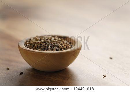 cumin zira seeds in wood bowl on table, shallow focus