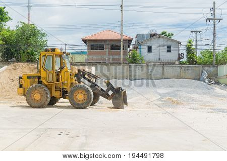 Yellow Hydraulic Tractor Loader or Backhoe earthmover woking in Construction site for Stone and Sand Grading
