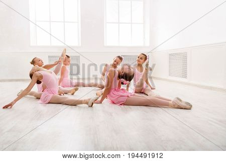 Little girls dancing ballet in studio. Young ballerinas stretching before performance, classical dance school