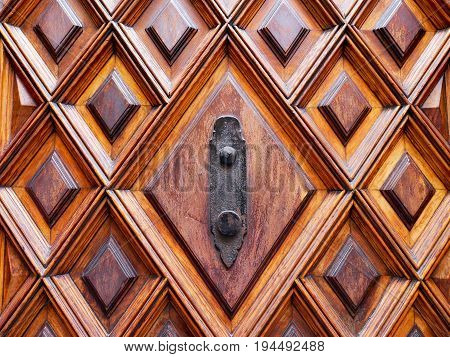 Close-up part of wooden door with black color metal door knob wall hook.
