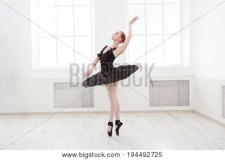 Beautiful graceful ballerina in black swan dress. Young ballet dancer practicing before performance in black tutu, classical dance studio, copy space