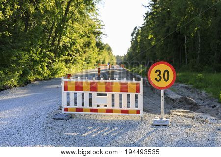 Road block and a speed limit sign on a road under construction