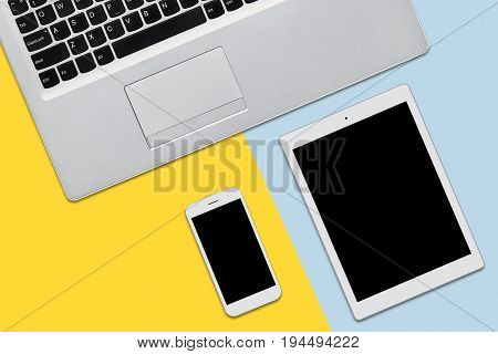 View From Above Of Modern Laptop Computer, Tablet And Smart Phone Lying On Flat Surface. Minimalisti