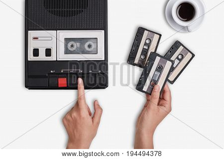 Retro Tape Recorder, Cassettes And Cup Of Hot Coffee Standing On White Surface. Hands Switching On C