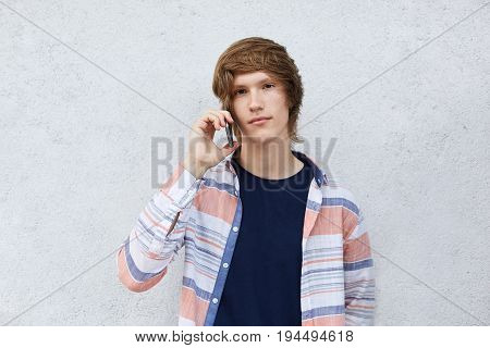 Hipster Boy With Dark Eyes And Stylish Hairstyle Having Serious Expression Calling His Mother Over S