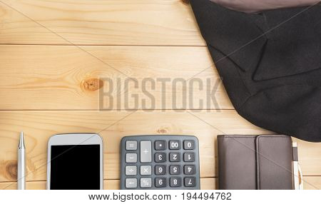 Office table with pen wallet calculator suit and smart-phone. View from above with copy space.