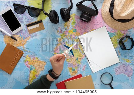 Plane travel planning on map top view. Preparation for vacation, trip abroad, tourist stuff on map background
