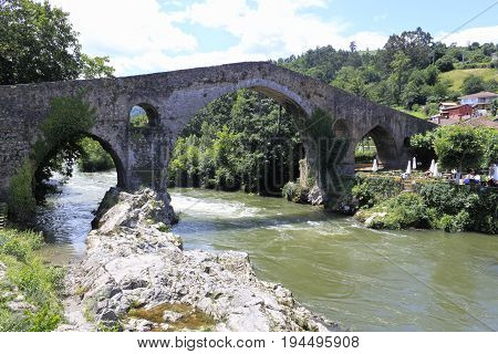 River With Current Passing By Roman Bridge In Cangas De Onís, Spain