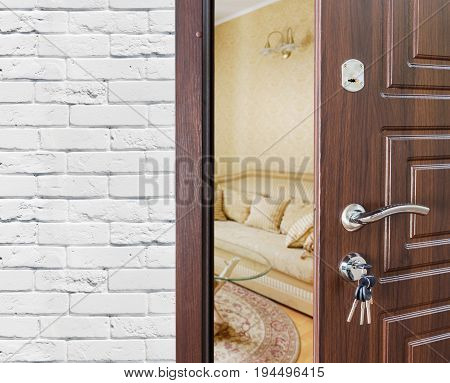 Half opened door, entrance to a living room. Welcome, privacy concept. Door lock with keys, white brick wall, modern interior design.